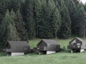 Immerse yourself within these black wood cabins near the forest in Nova Ponente, Italy